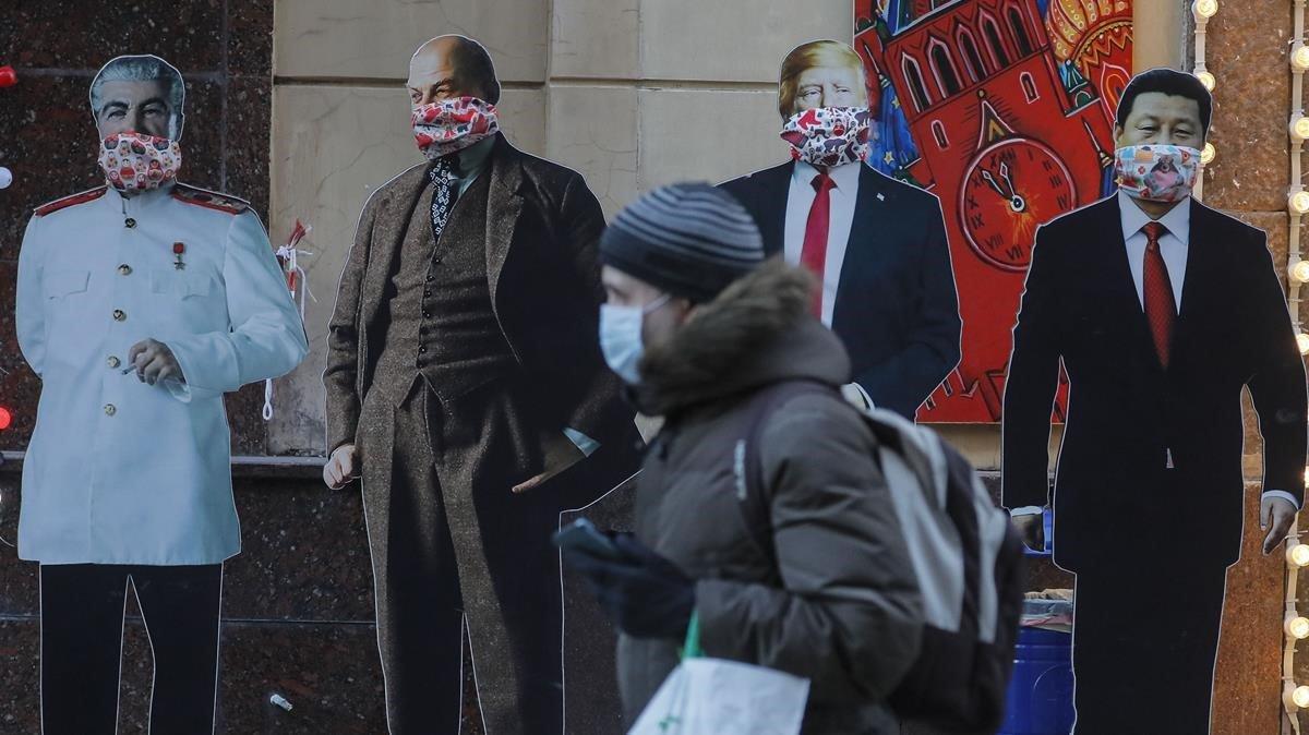 Un ciudadano con mascarilla pasa junto a la réplica de líderes mundiales en Moscú.
