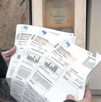 Un cliente con tres facturas de electricidad junto a un contardor.