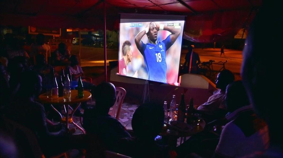 Un grupo de personas sigue la retransmisión televisiva de la final de la Eurocopa, Francia-Portugal, en un establecimiento público.