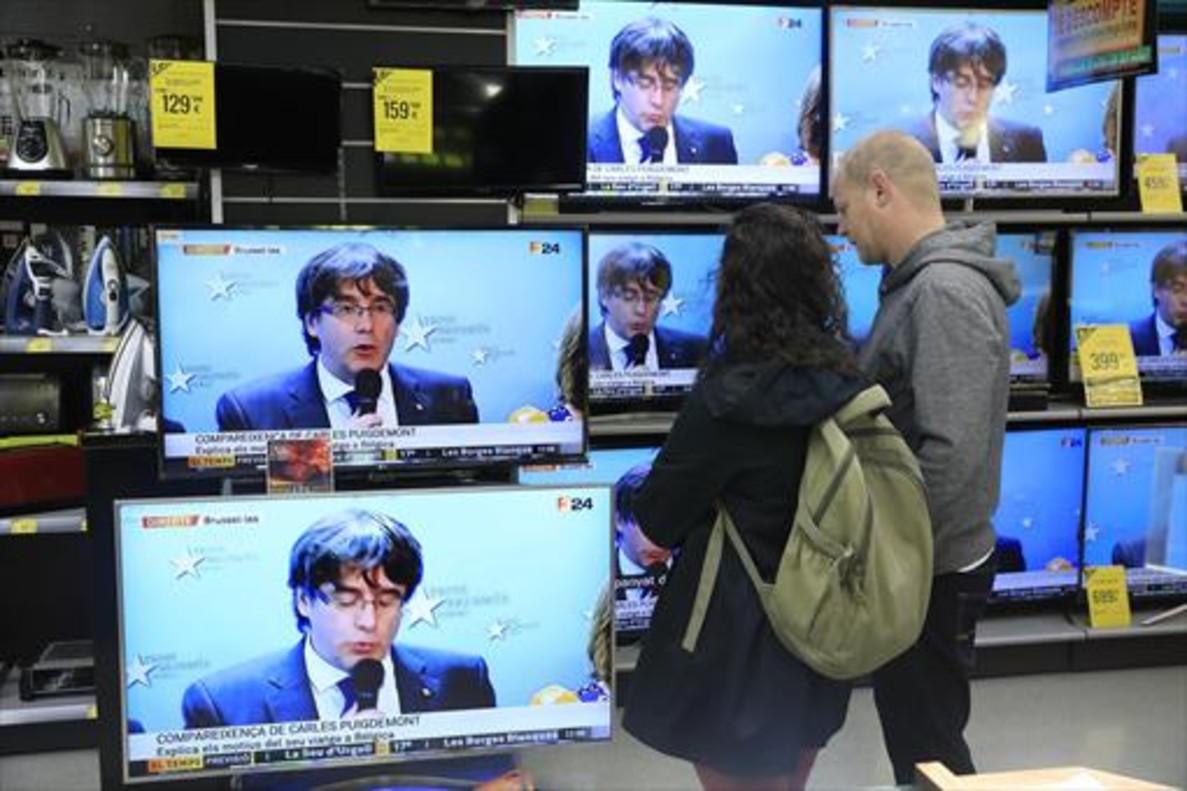 Expectación 8 Una pareja sigue la rueda de prensa de Puigdemont en una tienda del Poblenou.