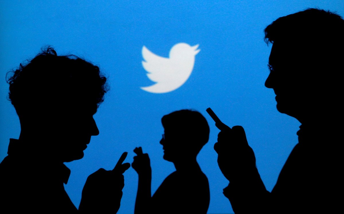 FILE PHOTO People holding mobile phones are silhouetted against a backdrop projected with the Twitter logo in this illustration picture taken September 27 2013 REUTERS Kacper Pempel Illustration File Photo