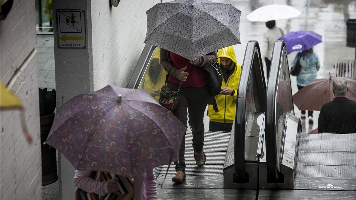 Personas protegiéndose de la lluvia en Barcelona.
