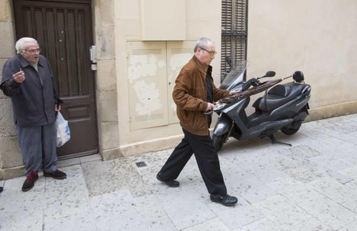 Figuerola pasa junto a un vecino alabandonar la finca en la que vive, este miércoles.