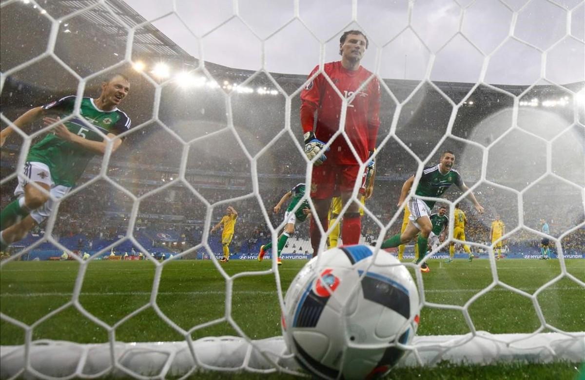Jonny Evans celebra el primer gol anotado por Irlanda del Norte anteGareth McAuley y el portero de Ucrania, Andriy Pyatov.