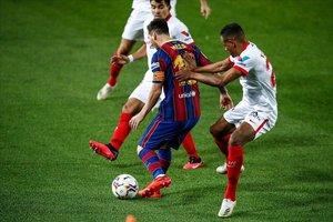 Leo Messi lucha el balón ante dos jugadores del Sevilla