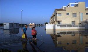 Unos vecinos caminan por una calle anegada de Dolores (Alicante).