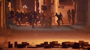 Manifestantes lanzan piedras contra las fuerzas de seguridad en el distrito de Djebel Lahmer, en Túnez, el 10 de enero.