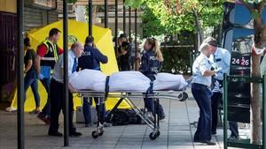 Miembros del servicio funerario trasladan el cadáver de la mujer asesinada en Madrid.