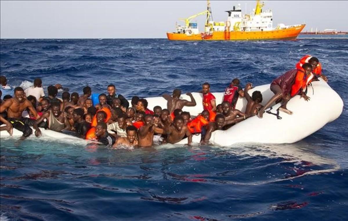 Momento en que varios inmigrantes son rescatados el lunesen alta mar cerca de la costa italiana.