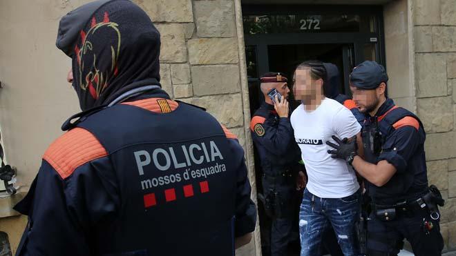 Operación policial en el barrio de Navas contra un grupo que distribuïa cocaína a lateros de Barcelona. En la foto, unos agentes se llevan a un detenido.