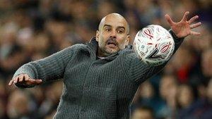 Pep Guardiola trata de atrapar el balón en la banda.