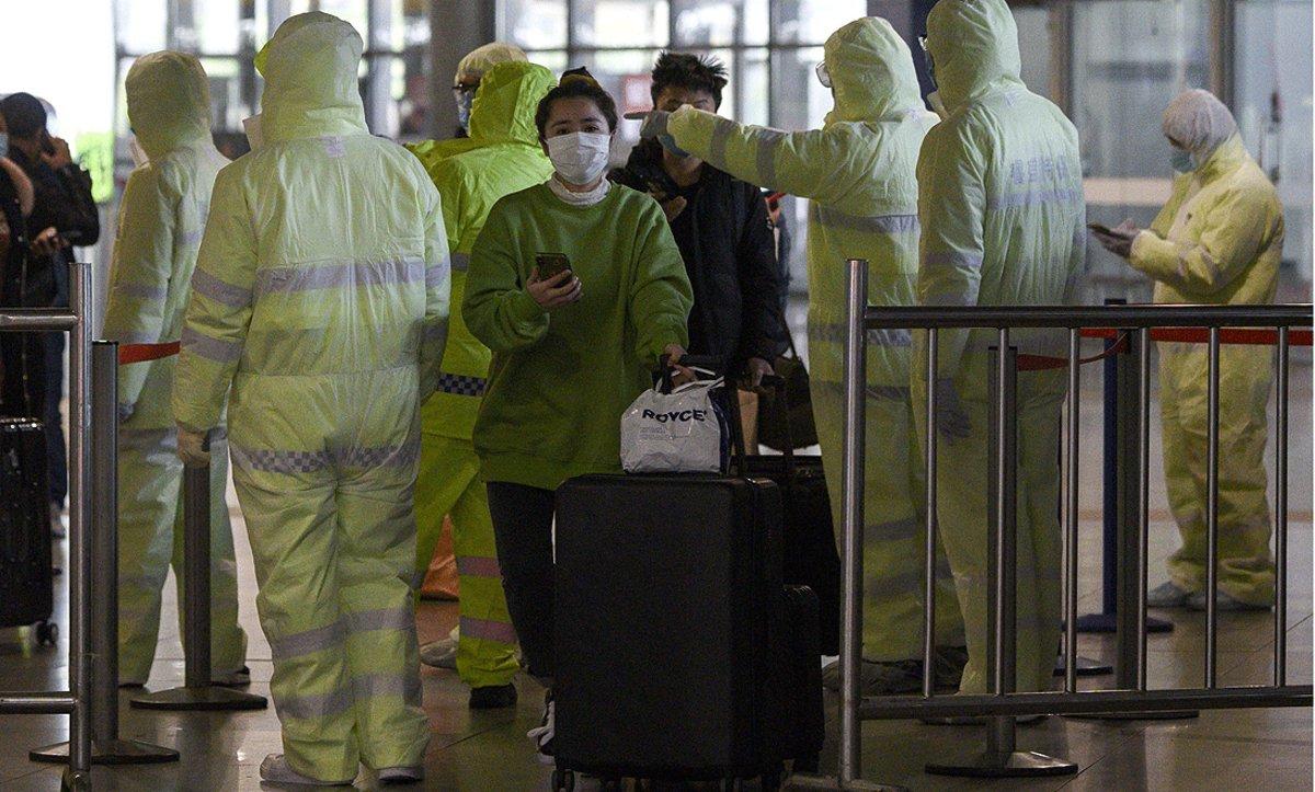 Personal médico controla el acceso depasajeros en una estación de trenes de Shanghái, este sábado.