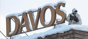 Un policía vigila desde un tejado en la víspera de la inauguración del 47º Foro Económico Mundial de Davos (Suiza), que comienza hoy.