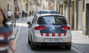 Un coche de los Mossos d'Esquadra patrulla por el barrio del Raval de Barcelona.