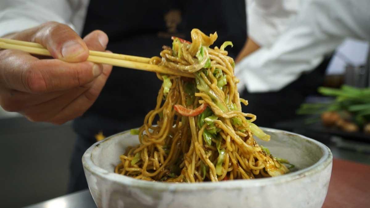 El chef de Grupo Nomo Naoyuki Haginoya explica cómo el yakisoba en un saco de tortilla.