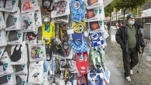 Un dublinense camina ayer martesfrente a una tienda que vende marcarillas en la capital irlandesa.