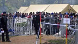 Refugiados controlados por agentes de policía en el saturado centro de acogida de Brezice, este miércoles.