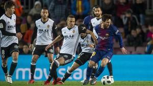 Messi, presionado por varios jugadores del Valencia.