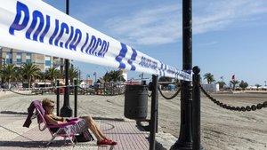 Una mujer toma el sol en el paseo marítimo de San Pedro de Pinatar ante la prohibición de entrar en la arena de la playa, el jueves pasado.