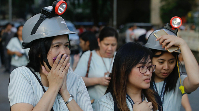 Trabajadores evacuados con casco de proteccion en las calles de Manila.