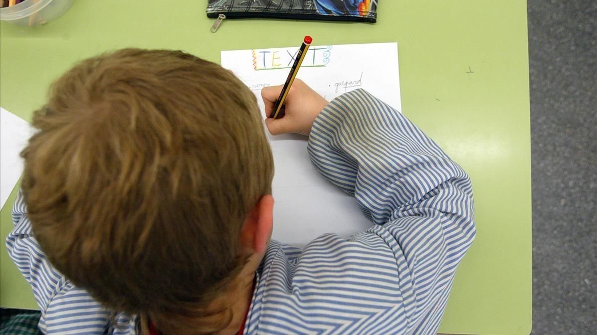 Un escolar aprende a escribiren un centro de Barcelona.