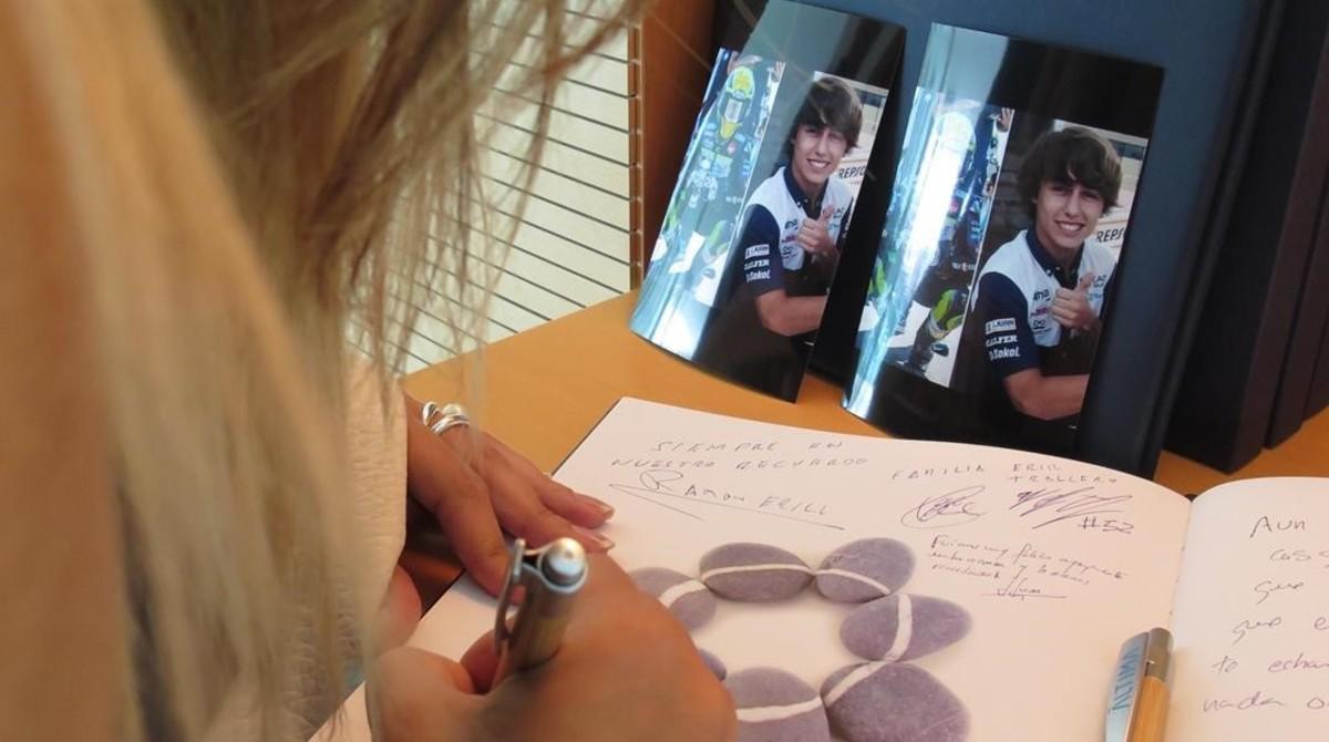 Una mujer estampa su firma en el libro de Andreas Pérez, en el Tanatorio de Ronda de Dalt.