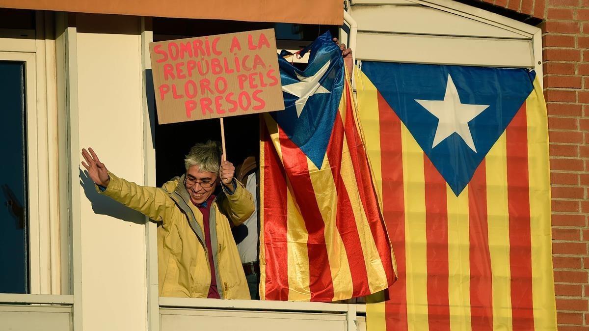 Una mujer exhibe una pancarta reclamando la libertad de los presos desde una ventanaal paso de la manifestación.