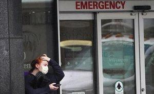 Una mujer se protege con una mascarilla en el acceso a la sala de urgenciasde un hospital en Nueva York.