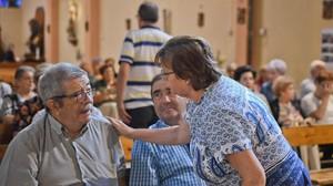 Roque Oriol recibe el consuelo de una mujer allegada durante un servicioreligioso en memoria de su esposa fallecida.