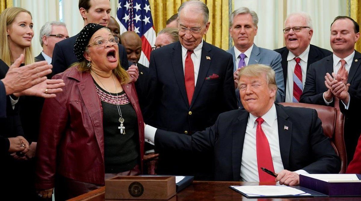 Donald Trump toca a Alveda King, evangelista y sobrina de Luther Martin King, que habló durante la ceremonia de la firma de la Ley Primer Paso, en el Despacho Oval de la Casa Blanca, el 21 de ediciembre del 2018.