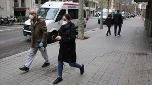 Transeúntes con mascarillas por las calles de Barcelona.
