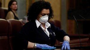 Una trabajadora de la limpieza desinfecta el atril, tras la intervención del presidente del Gobierno, Pedro Sánchez, para explicar la declaración del estado de alarma y las medidas para paliar las consecuencias de la pandemia.