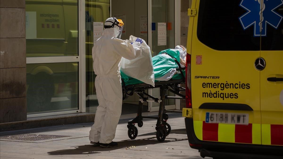 Un sanitario traslada a un paciente covid-19 en ambulancia.