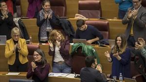 Diputados valencianos, entre ellos la vicepresidenta Mónica Oltra y el conseller de educación Vicent Marzà, aplauden tras la aprobación de la ley