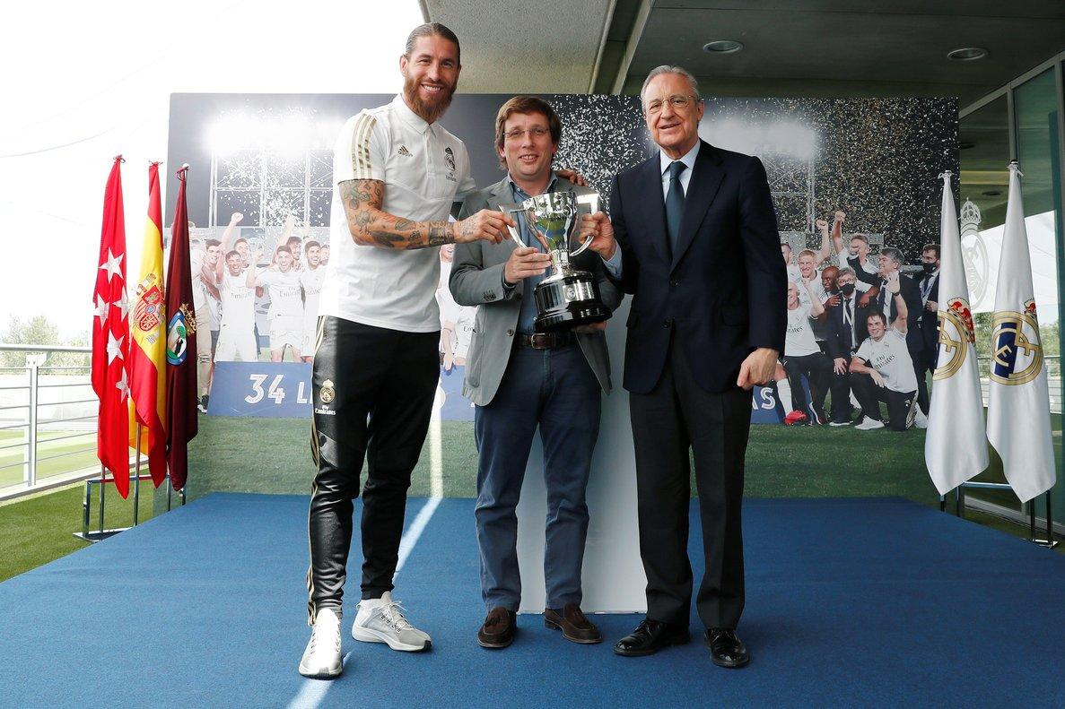 El alcalde de Madrid, José Luis Martínez Almeida (c), posa junto a Florentino Pérez (d) y a Sergio Ramos con el trofeo de la Liga.