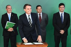 Brazilian President Jair Bolsonaroaccompanied by Chief of Staff Onyx LorenzoniVice-President Hamilton Mourao2 and Justice Minister Sergio Morosmiles as he signs a presidential decree that flexibilizes the possession of firearmsat Planalto Palace in BrasiliaPhoto by EVARISTO SAAFP
