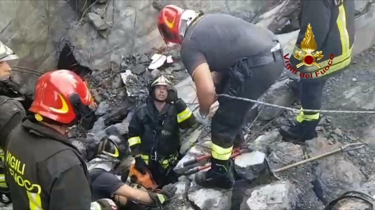 Los bomberos italianos realizando tareas de rescate en los escombros del puente.