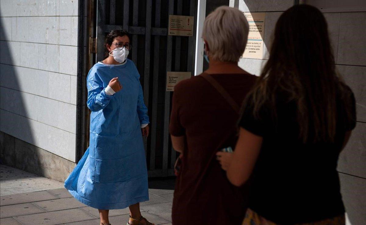 Una sanitaria habla con pacientes que esperan en el exterior de un centro médico de Santa Coloma de Gramenet para realizarse el test de coronavirus.