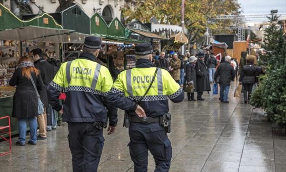 Dos agentes de la Guardia Urbana patrullan ayer por el mercado de santa Llúcia.