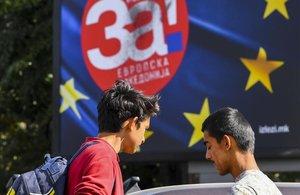 Dos chicos macedonios conversan junto a unos carteles con la bandera de la UE de la campaña a favor del 'sí' al referéndum.