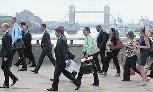 Empleados de la City londinense atraviesan el puente de Londres para dirigirse al trabajo, el pasado agosto.