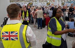 Empleados del Gobierno británico atienden, en el aeropuerto de Palma de Mallorca, a pasajeros afectados por la quiebra de Thomas Cook.