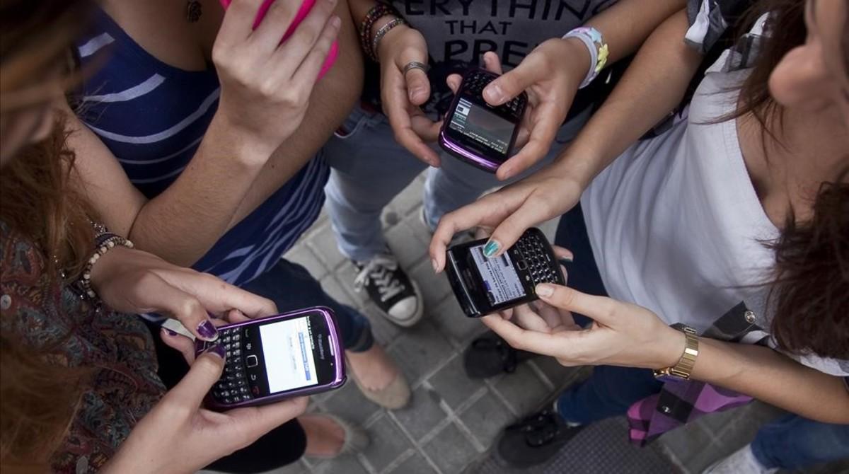 Estudiantes de secundaria con sus móviles.