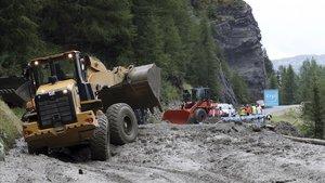 Excavadoras tratan de limpiar la carretera para el paso del Tour de Francia.
