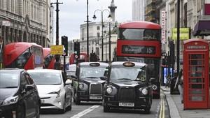 Coches, taxis y autobuses pasan por delante de los Reales Tribunales de Justicia cerca de Trafalgar Square, en Londres, este miércoles.