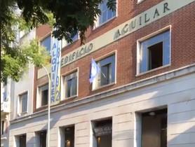 El emblema de Hogar Social Madrid, en una de las ventanas del nuevo edificio okupado, las antiguas oficinas de la Editorial Aguilar.