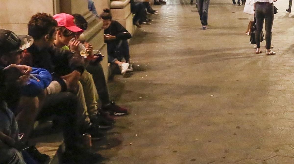 Un chico esnifa cola sentado en la parte exterior de la tienda Apple, en el paseo de Gràcia.