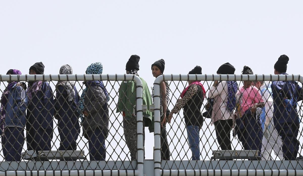 Inmigrantes hacen cola en el puerto italiano de Augusta.