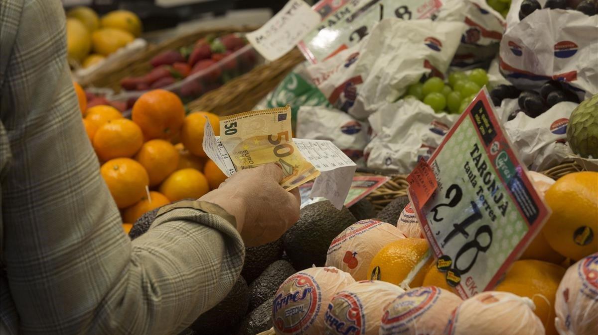 Una mujer paga por la compra de unos alimentos en un mercado de Barcelona.