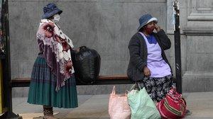 Mujeres esperan el autobús en una calle de La Paz, la capital de Bolivia.